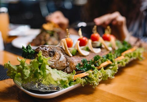 Close-up vista de peixe robalo cozido decorado com tomate cereja e rodelas de limão na alface em uma bandeja de madeira
