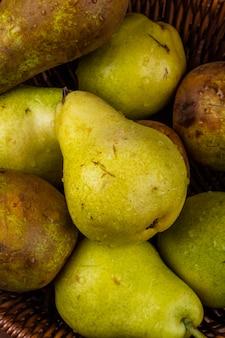 Close-up vista de peras maduras frescas com gotas de água em uma cesta de vime