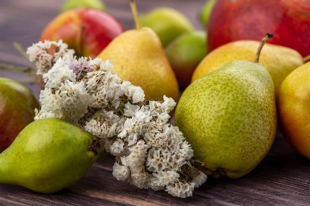 Close-up vista de pêssegos e flores com maçã e romã na superfície de madeira