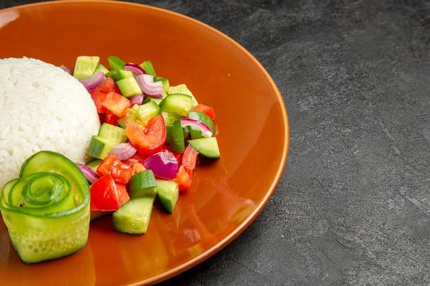 Close-up vista de prato de arroz caseiro e salada com tomate e pepino na mesa escura
