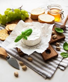 Close-up vista de queijo camembert, uva, nozes e mel em uma tábua na mesa branca