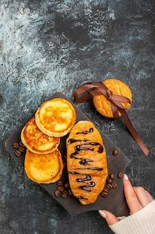 Close-up vista de saboroso café da manhã com croisasant panquecas biscoitos empilhados na superfície escura