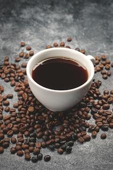 Close-up vista de sementes de café marrom com xícara de café escuro