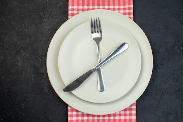 Close-up vista de talheres de aço inoxidável colocados em pratos vazios brancos em uma toalha vermelha listrada em fundo preto com espaço livre