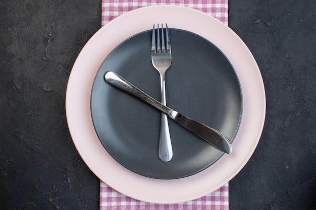 Close-up vista de talheres de aço inoxidável colocados em pratos vazios de cerâmica colorida em toalha dobrada despojada rosa sobre fundo preto com espaço livre