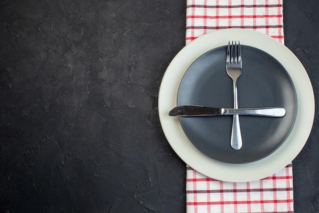 Close-up vista de talheres definido em cor cinza escuro e pratos vazios brancos em toalha listrada de vermelho sobre fundo preto