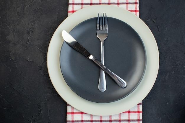 Close-up vista de talheres definido em cor cinza escuro e pratos vazios brancos em toalha vermelha listrada em fundo preto com espaço livre