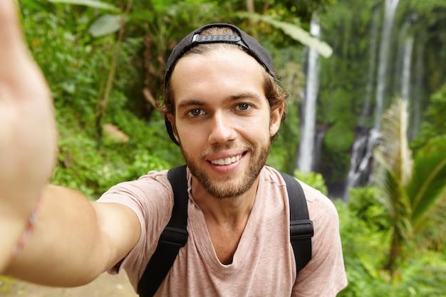 Close-up vista de um alpinista caucasiano bonito usando snapback olhando com um sorriso feliz enquanto tira uma selfie com uma paisagem incrível com cachoeira