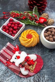 Close-up vista de um delicioso acessório de decoração de biscoito meia de papai noel e cornell em uma tigela ramos de abeto na superfície escura