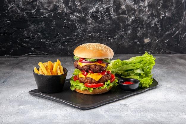 Close-up vista de um delicioso sanduíche caseiro e garfo ketchup fritas verdes na bandeja preta na superfície cinza angustiado