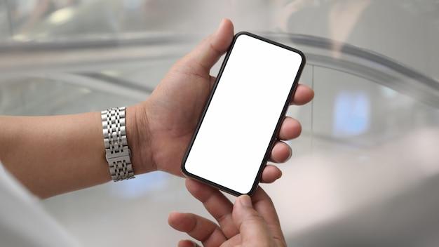 Close-up vista de um homem segurando o smartphone de tela em branco na sala de parede de vidro