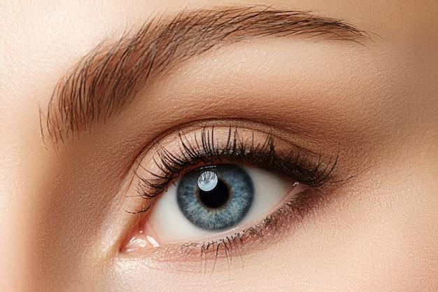 Close-up vista de um lindo olho feminino azul. boa visão, lentes de contato, confiança ou conceito de observação