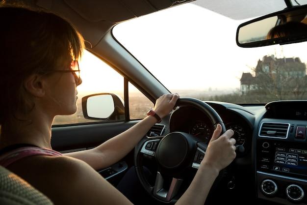 Close-up vista de um motorista de mulher segurando o volante de um carro ao pôr do sol.