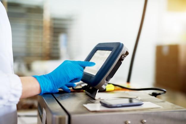 Close-up vista de um painel de controle touchscreen de grande máquina usada por um trabalhador em um pano estéril.