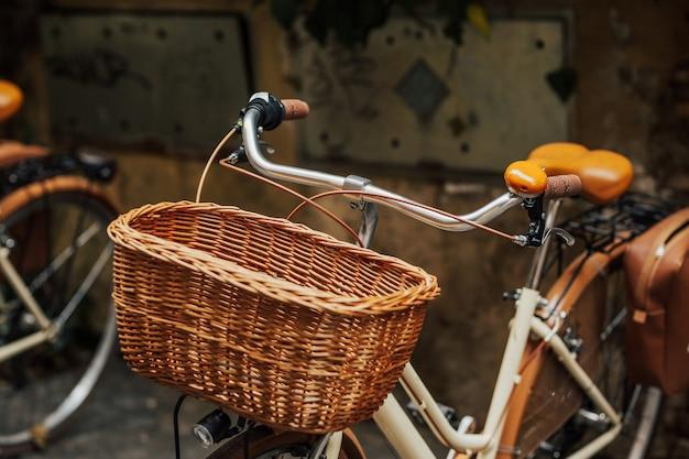 Close-up vista de uma cesta trançada marrom em uma bicicleta, estilo vintage retrô.