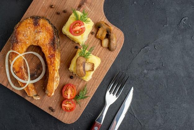 Close-up vista de uma deliciosa farinha de peixe frito e tomates verdes cogumelos em talheres de tábua de madeira na superfície preta