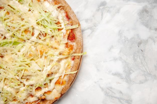 Close-up vista de uma deliciosa pizza vegana caseira no lado direito em uma superfície branca manchada com espaço livre