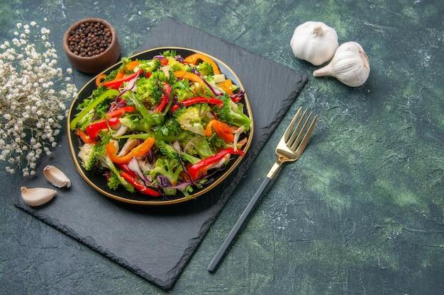 Close-up vista de uma deliciosa salada de vegetais com vários ingredientes em uma tábua de corte preta