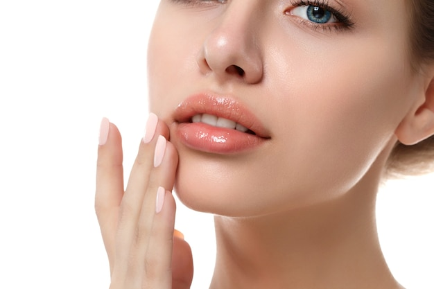 Close-up vista de uma jovem e bela mulher caucasiana tocando seus lábios isolados sobre fundo branco