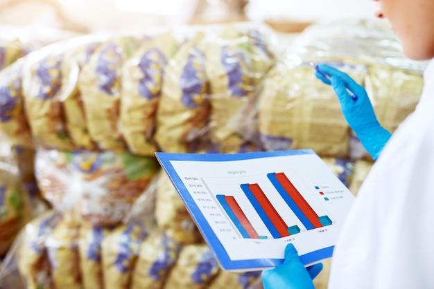 Close-up vista de uma jovem trabalhadora mãos segurando e inspecionando a folha de gráfico e comparando-a com pilhas de produtos armazenados na fábrica.