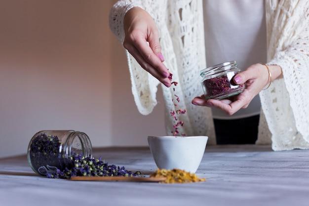 Close-up vista de uma mão de mulher espalhando rosas secas folhas em uma tigela com água. colher com açafrão amarelo e uma tigela com folhas secas roxas em cima da mesa