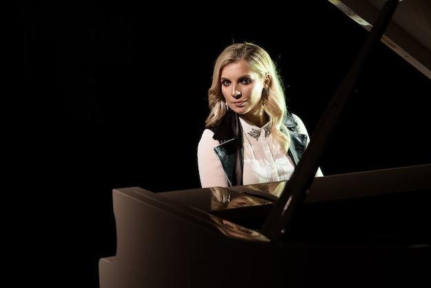 Close-up vista de uma menina toca piano na sala de concertos em cena