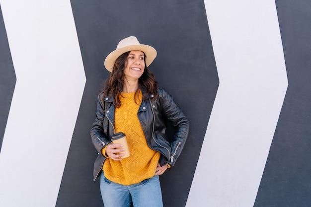 Close-up vista de uma mulher adulta bebendo uma xícara de café reciclada ao ar livre.