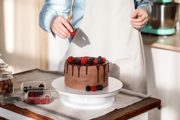 Close-up vista de uma mulher decorando o bolo de chocolate