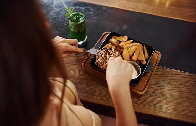 Close-up vista de uma mulher que come fast food dentro de casa no café.