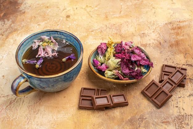 Close-up vista de uma xícara de chá quente de ervas e barras de chocolate na mesa de cores misturadas