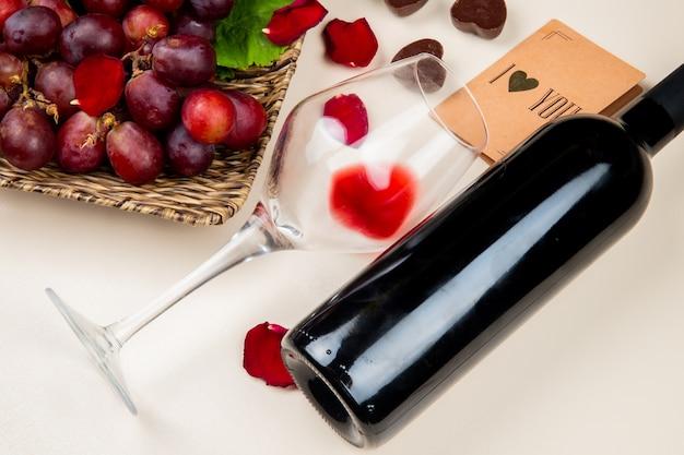 Close-up vista de vidro e garrafa de vinho tinto e uva com eu te amo cartão na mesa branca decorada com pétalas de flores