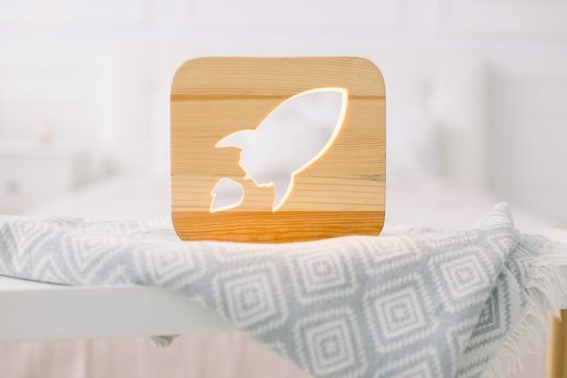 Close-up vista do abajur de madeira aconchegante com imagem recortada de foguete, no cobertor cinza no interior aconchegante do quarto claro
