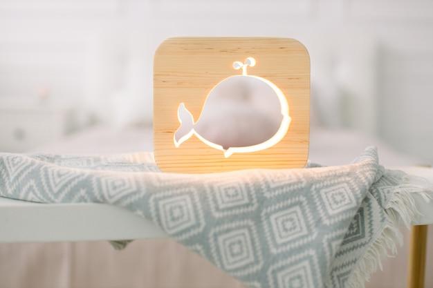 Close-up vista do acolhedor abajur de madeira com imagem recortada de baleia, no cobertor cinza no interior do quarto aconchegante de luz.