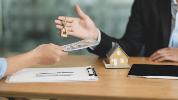 Close-up vista do agente imobiliário dando a chave da casa para seu cliente