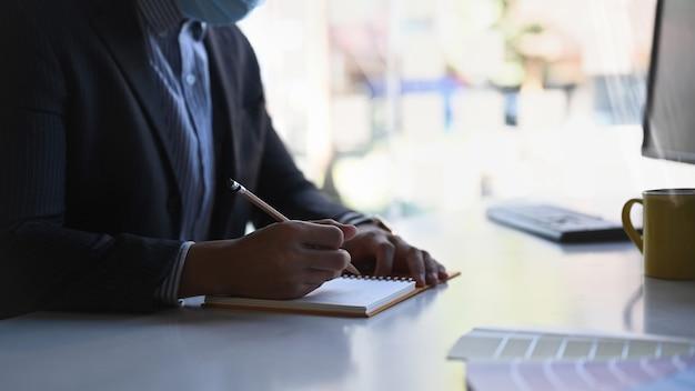 Close-up vista do arquiteto segurando a caneta para escrever informações no caderno em seu espaço de trabalho.