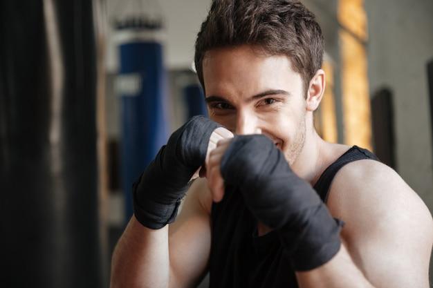 Close-up vista do boxeador sorridente fazendo exercício no ginásio