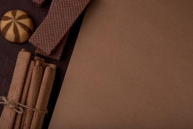Close-up vista do caderno com biscoitos diferentes em torno de palitos crocantes, amarrados com uma corda e waffles de chocolate no fundo escuro