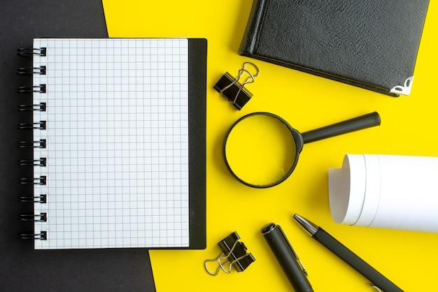 Close-up vista do caderno espiral branco em branco lupa canetas em fundo preto e amarelo misturar cores