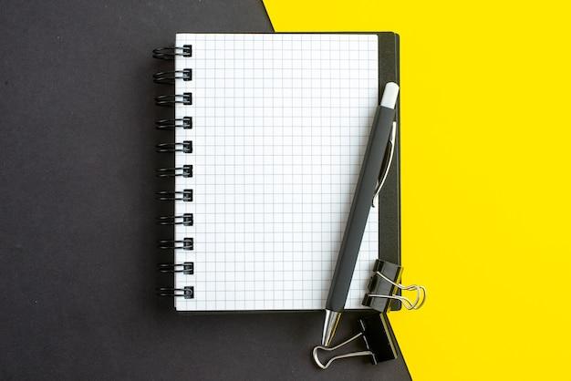 Close-up vista do caderno espiral no livro e canetas no fundo amarelo preto com espaço livre