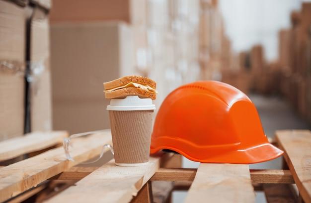 Close-up vista do capacete de cor laranja, copo de bebida e sanduíche no armazém.