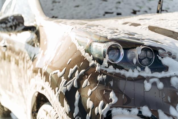 Close-up vista do carro preto lavado por alta pressão de água e sabão na lavagem do carro. conceito de serviço de limpeza. estação de lavagem automática de autoatendimento