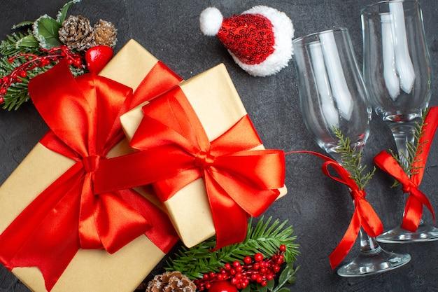Close-up vista do clima de natal com belos presentes com fita em forma de arco e ramos de abeto acessórios de decoração chapéu de papai noel taças de vidro cones de coníferas em um fundo escuro