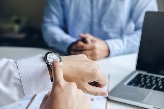 Close-up vista do empresário apontando por lado relógio de pulso