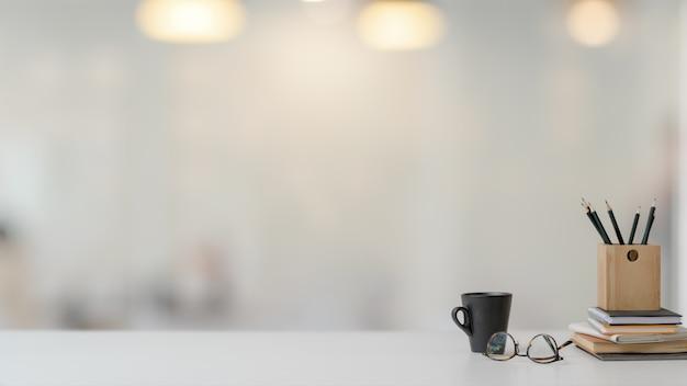 Close-up vista do espaço de trabalho com artigos de papelaria, copos e xícara de café na mesa branca com fundo desfocado