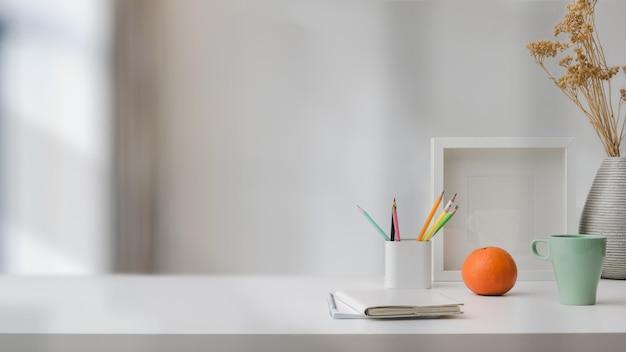 Close-up vista do espaço de trabalho com espaço de cópia, artigos de papelaria, xícara de café e decorações na mesa branca com fundo desfocado