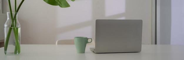 Close-up vista do espaço de trabalho com o laptop, caneca e vaso de planta na mesa branca ao lado da janela
