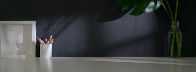 Close-up vista do espaço de trabalho da moda com moldura de mock-up, artigos de papelaria, decorações e espaço de cópia