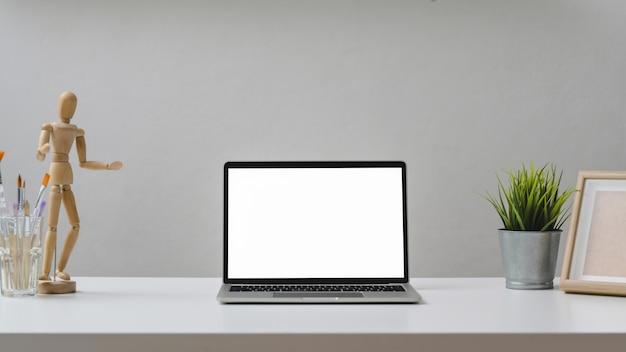 Close-up vista do espaço de trabalho de design com laptop, figura de madeira, ferramentas de pintura e decorações com mesa