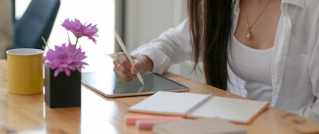 Close-up vista do estudante universitário feminino escrevendo sobre tablet digital com caneta stylus