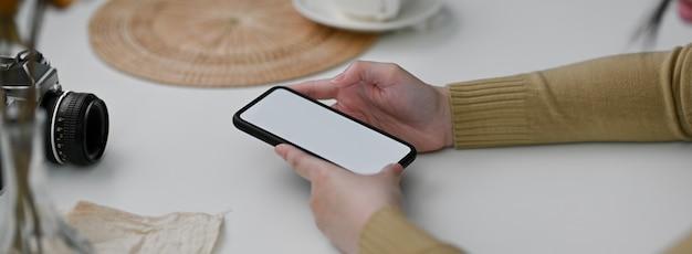 Close-up vista do fotógrafo feminino usando smartphone mock-up para entrar em contato com o cliente